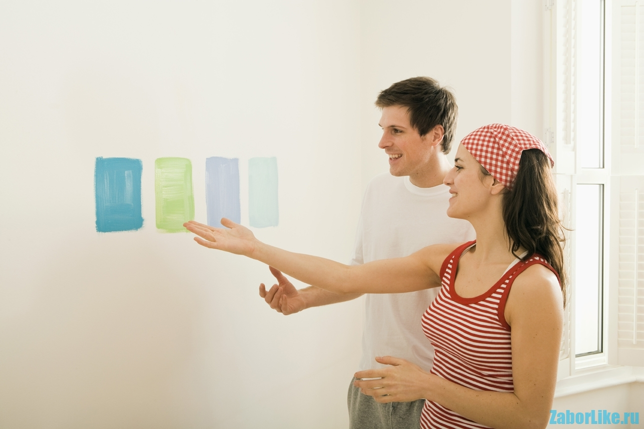 Couple choosing color swatches on wall
